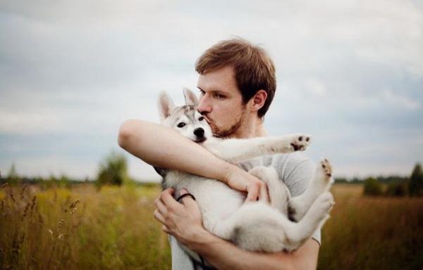 Парень держит на руках щенка