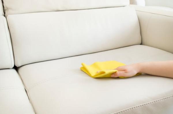 Светлый диван протирают тряпкой
